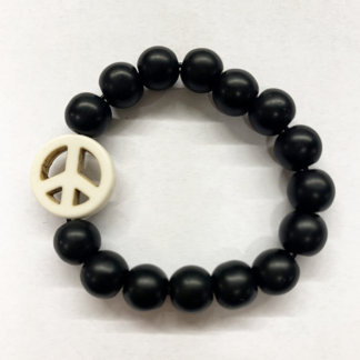 a bracelet made with black onyx beads with one white bead in the shape of a peace sign