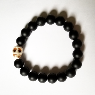 a bracelet made with black onyx beads with one white bead in the shape of a skull